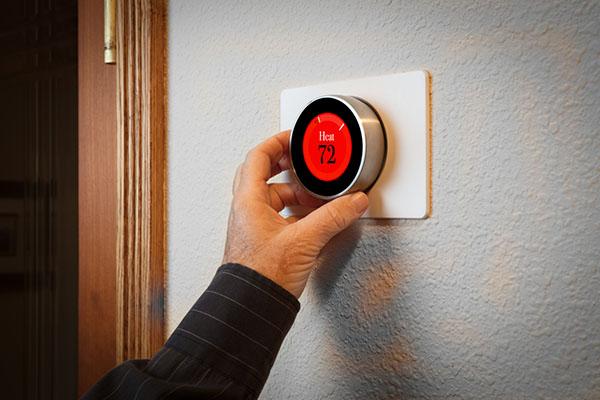 man adjusts smart thermostat
